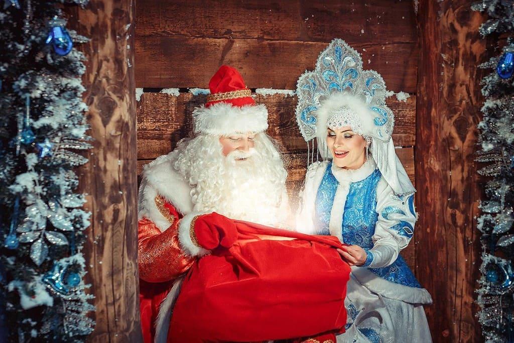 Дед Мороз и Снегурочка смотрят в мешок с подарками